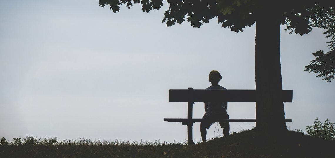 A person sitting in a bench feeling lonely looking for ways on how to overcome this feeling