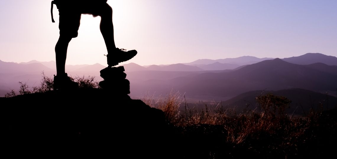 A man in top of a mountain enjoying the process