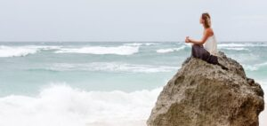Girl practicing mindfulness by meditating in a beach